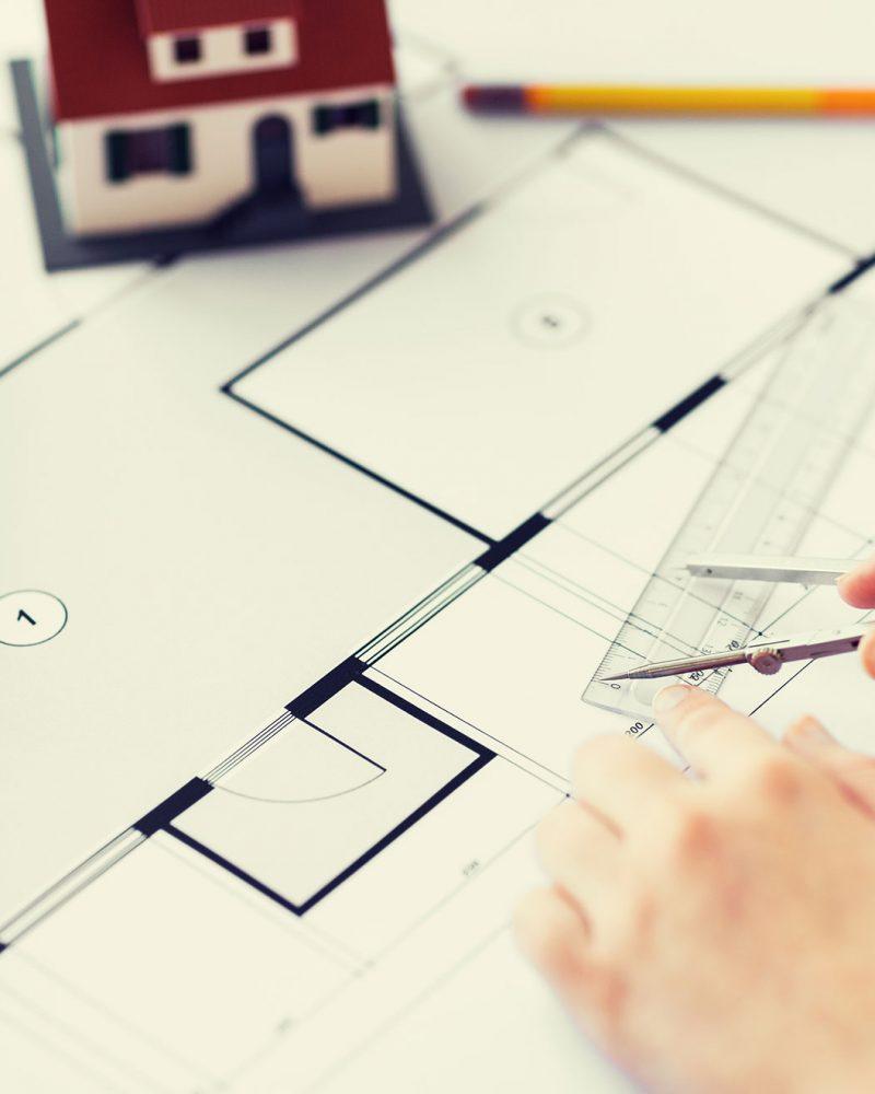 close-up-of-hands-with-compass-measuring-blueprint-PWKRVTA-rcarquitetura-apresentacao